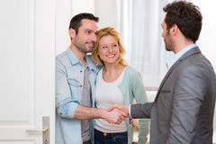 Young happy couple handshaking real estate agent after signing c. View of a Young happy couple handshaking real estate agent after signing contract Stock Images