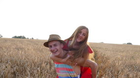 Young, happy couple have a piggy back in the field stock footage