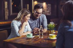 Young happy couple having coffee in cafe and looking at phone. royalty free stock photography