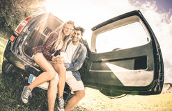 Young happy couple having fun with mobile phone at car road trip Royalty Free Stock Photo