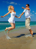 Young happy couple having fun on sea beach Stock Photos