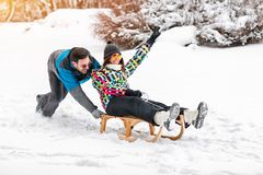 Young couple having fun on snowy day, sledding and smiling together stock image