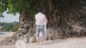 Young happy couple having fun holding hands spinning around on the beach next to the tree with beautiful roots. Slow stock video