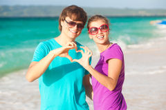 Young happy couple having fun on tropical beach. Royalty Free Stock Image