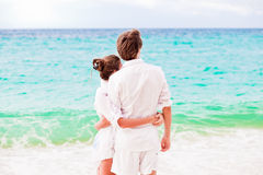 Young happy couple having fun on tropical beach. honeymoon. Young happy couple in white having fun on tropical beach. honeymoon concept Royalty Free Stock Photography