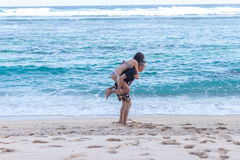 Young happy couple having fun on a tropical resort`s white beach of Bali island, Indonesia. royalty free stock photography