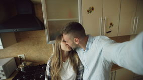 Young happy couple having online video chat in the kitchen at home stock video