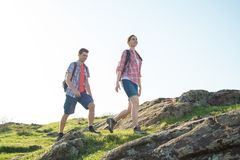 Young Happy Couple Hiking with Backpacks on the Beautiful Rocky Trail at Sunny Evening. Family Travel and Adventure. Royalty Free Stock Images