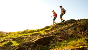 Young Happy Couple Hiking with Backpacks on the Beautiful Rocky Trail at Sunny Evening. Family Travel and Adventure. stock photo