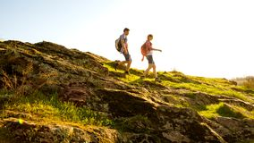 Young Happy Couple Hiking with Backpacks on the Beautiful Rocky Trail at Sunny Evening. Family Travel and Adventure. Royalty Free Stock Photo