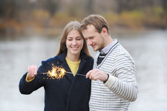 The young happy couple holding a bengal light on the river bank. Royalty Free Stock Photos