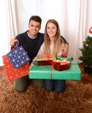Young Happy Couple holding Christmas Presents Stock Images