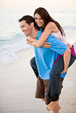 Young happy couple holding hands on beach Stock Images