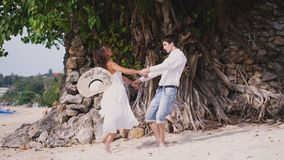 Young happy couple holding hands each other on the beach by the tree with beautiful roots. Woman wearing hat and white. Young happy couple running to meet each Stock Photos