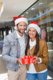 Young happy couple holding heart shaped boxes with christmas hats on their hats Stock Photography