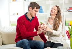 Young happy couple holding a piggy bank in the living room Royalty Free Stock Photos