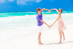 Young happy couple on honeymoon making heart shape. On tropical beach. This image has attached release Royalty Free Stock Photos