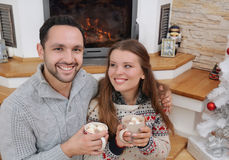Young happy couple with hot cocoa drink in comfy sweaters sittin. G near fireplace, happy holiday concept Stock Photography