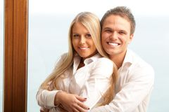 Young happy couple hugging at home. With a beautiful seaview behind their window Stock Image