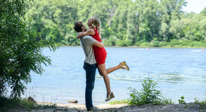 Young happy couple hugging and laughing on river background Royalty Free Stock Photos