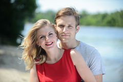 Young happy couple hugging and laughing on river background Royalty Free Stock Image