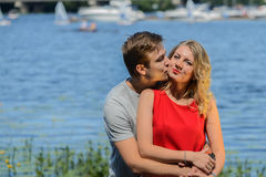 Young happy couple hugging and laughing on river background Stock Photos