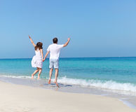 Young happy couple jumping on the beach Royalty Free Stock Photography