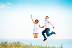 Young happy couple jumping on the beach Stock Photo