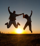Young happy couple jumping high in the air. On sunny summer day Stock Images