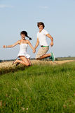 Young happy couple jumping outside in summer stock photo