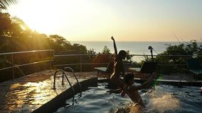 Young happy couple jumping in resort swimming pool during amazing sunset and splashing droplets underwater in slow stock video footage