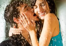 Young happy couple kissing. Young happy amorous couple kissing and hugging under a rain Royalty Free Stock Photography