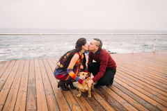 Young happy couple kissing each other and playing with dog on the rainy berth in autumn. Sea background.  Stock Photos