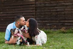 Young Happy Couple Kissing with English Bulldogs. A young, fashionable, engaged couple kisses with their two happy English Bulldogs royalty free stock images