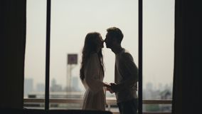 Young happy couple kissing and enjoying the view from a balcony overlooking city in morning during honeymoon Stock Photos