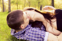 Young happy couple kissing. On the grass Stock Image