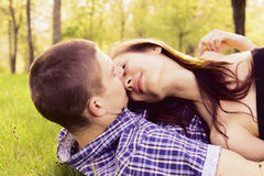 Young happy couple kissing. On the grass Stock Images