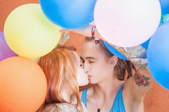 Young happy couple kissing and holding balloons Stock Images