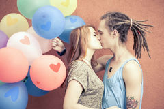 Young happy couple kissing and holding balloons Stock Photography