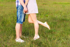 Young happy couple kissing in love, standing on the grass in the summer sun the night Stock Photos