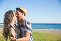 Young happy couple kissing outside. Portrait of young happy couple kissing outside Royalty Free Stock Image