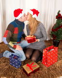 Young Happy Couple Kissing on rug at Christmas Stock Images