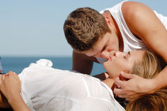 Young happy couple kissing by the sea royalty free stock photos