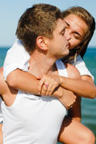 Young happy couple kissing by the sea outdoors. Young happy couple kissing by the sea in summer outdoors Royalty Free Stock Photo