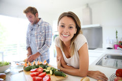 Young happy couple in the kitchen preparing meal Stock Photography