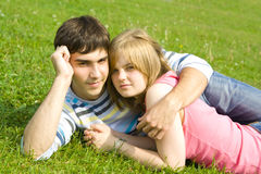 Young happy couple laying on a green grass Stock Photo