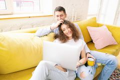 Free Young Happy Couple Lies On A Yellow Sofa With A Laptop In Their Apartment, Online Shopping And Internet Technology For Home Royalty Free Stock Photo - 162754545