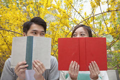 Young happy couple looking at each other over the top of their books, outdoors in spring Stock Image