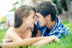 Young happy couple looking in each others eyes. Happy smiling couple beautiful young women & handsome young men lying outdoors on the green grass background royalty free stock images