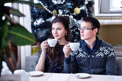 Young happy couple looking in one side holding a cup. Christmas tree Royalty Free Stock Photo